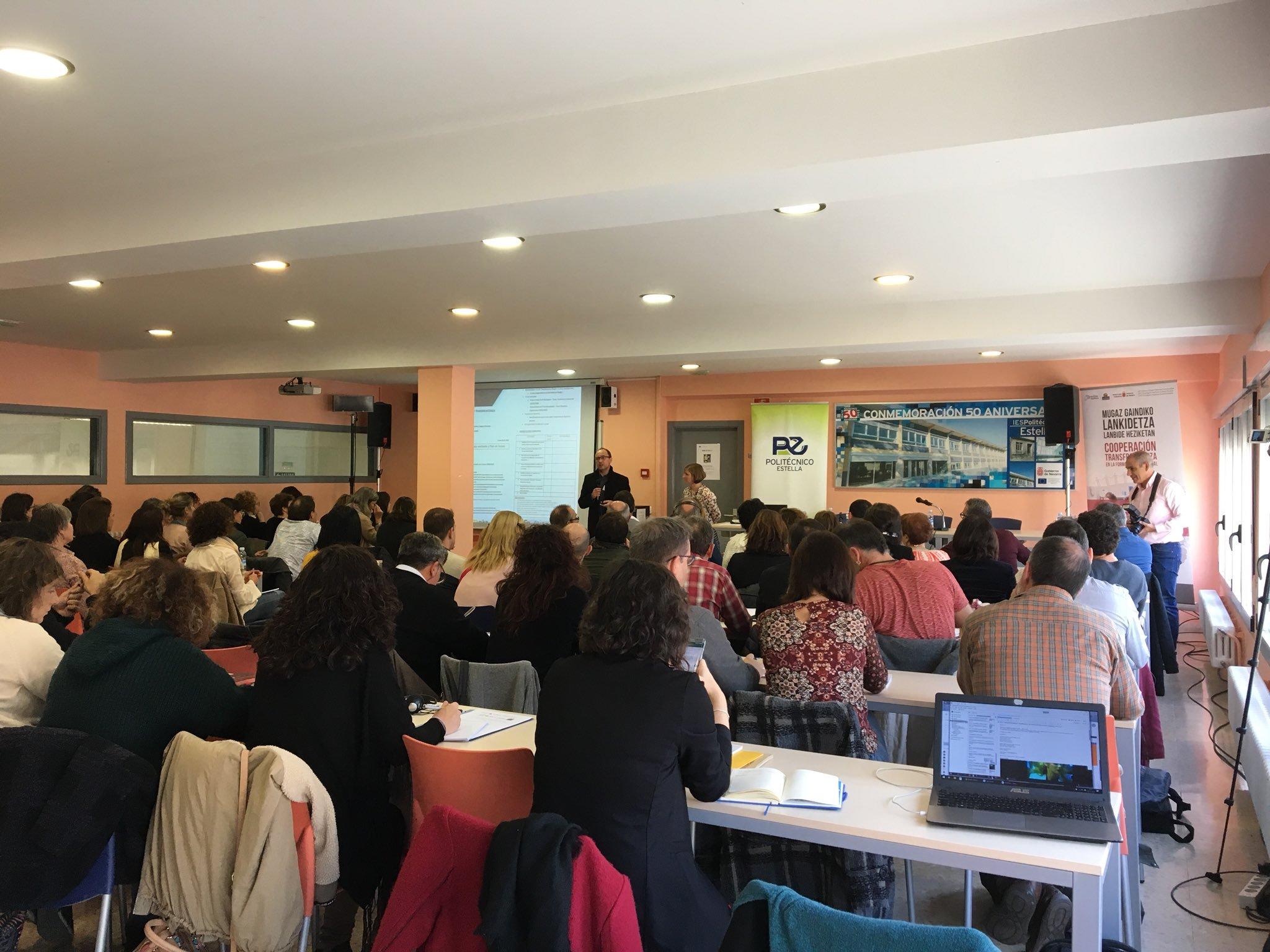 Imagen de personas dando la espalda a la cámara y atendiendo sentadas en filas, las explicaciones de un ponente en una aula grande y pintada de naranja.