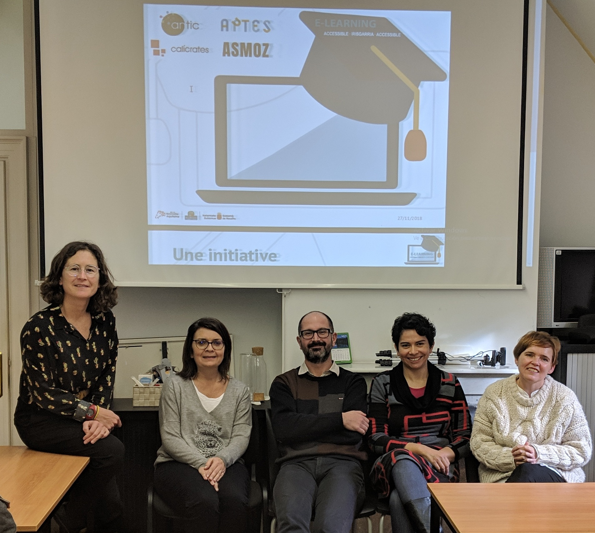 5 personas sentadas mirando a cámara, con la imagen del logo del proyecto de E-learning Accesible