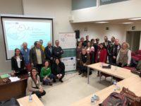 Imagen de 21 personas participantes en el seminario celebrado en Bilbao en noviembre de 2018, mirando a cámara junto al poster con el logo de EKIN.