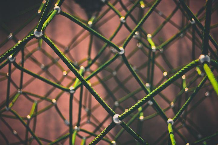 Una red en 3 dimensiones de cordón verde unido por unas bolitas plateadas.