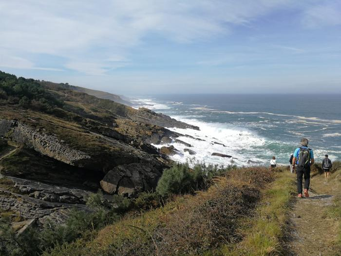 Personas andando por un camino al borde del mar