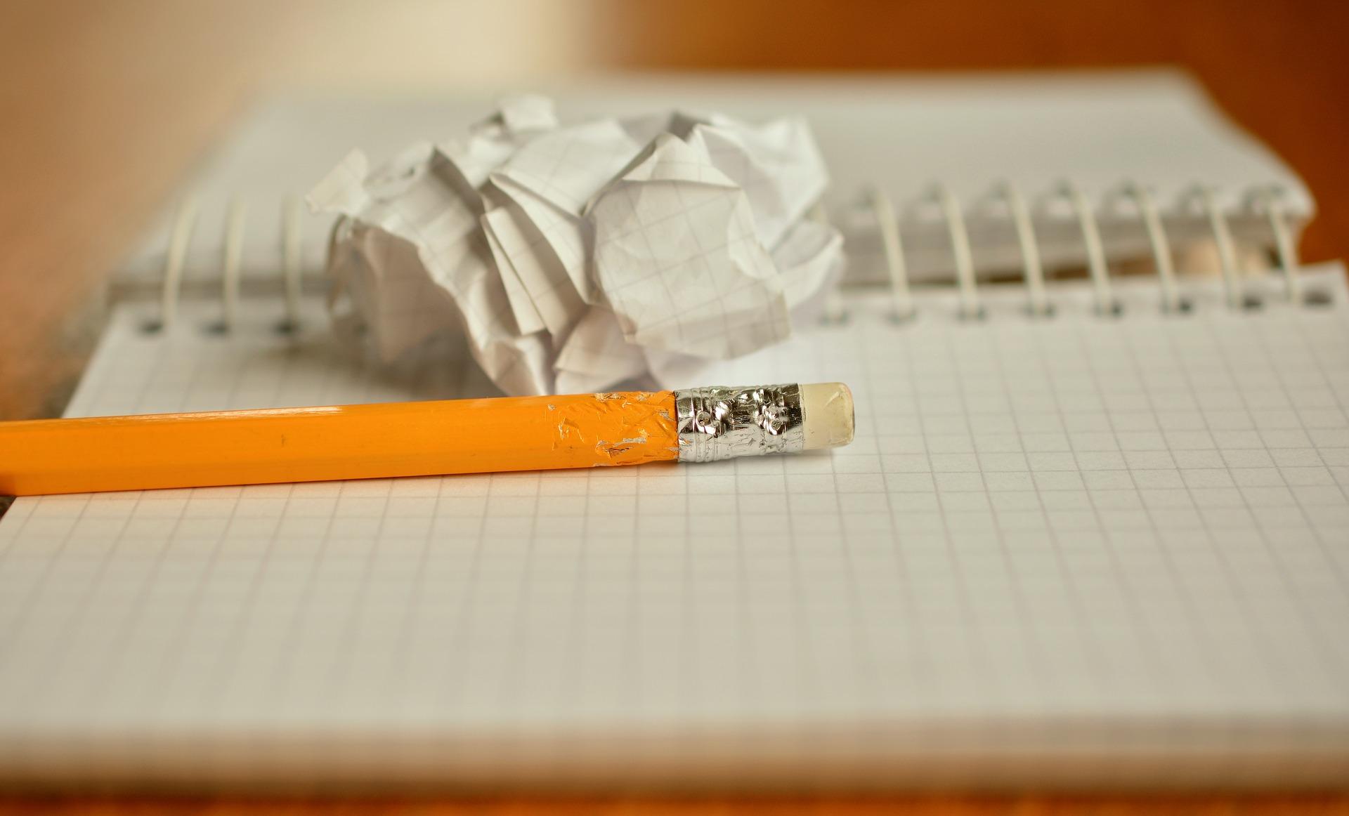 Un cuaderno en blanco abierto, con un lapiz amarillo sobre él y un papel a rrugado en una bola a su lado.
