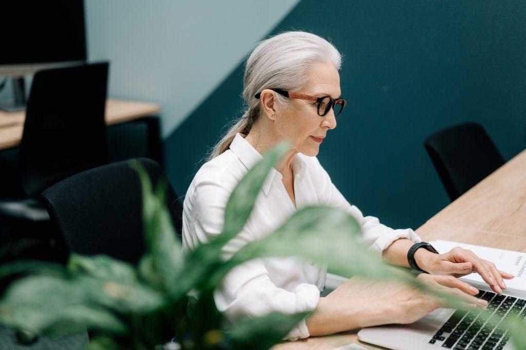 Mujer mayor con coleta, gafas y camisa blanca, utilizando un ordenador portátil.