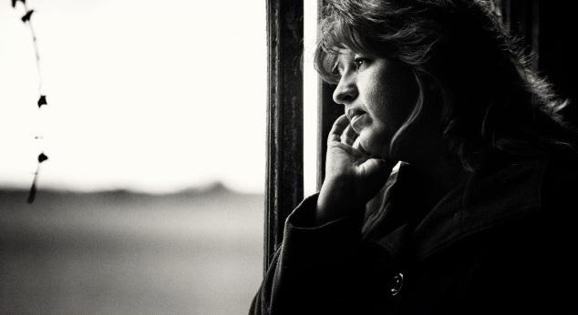 Imagen en blanco y negro de una mujer mirando por la ventana.