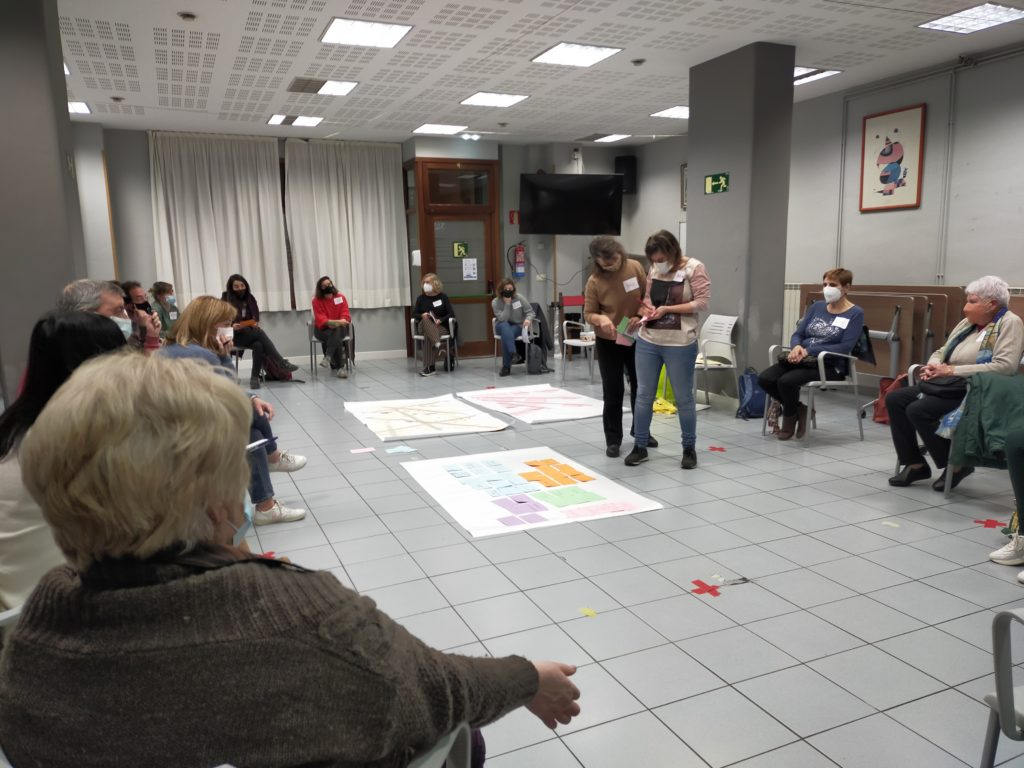 Personas sentadas en círculo y dos de ellas de pie en el centro, en la dinámica de Amara Berri.