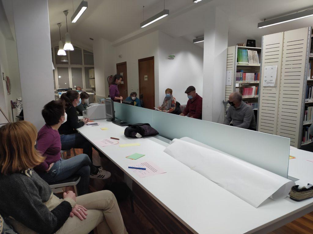Grupo de personas sentado al rededor de una mesa en la dinámica en Saiaz.