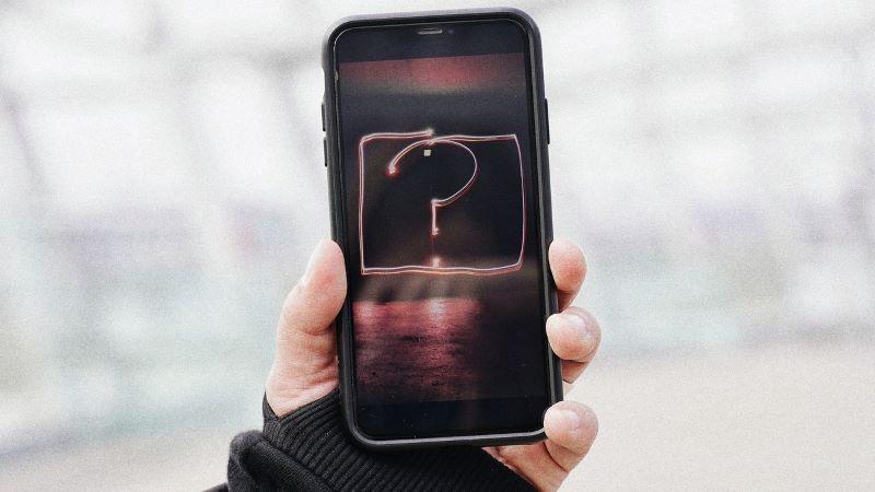 Una mano sostiene un móvil con un interrogante en la pantalla.