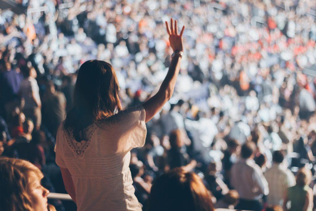 Una mujer de espaldas, levantando la mano en una multitud