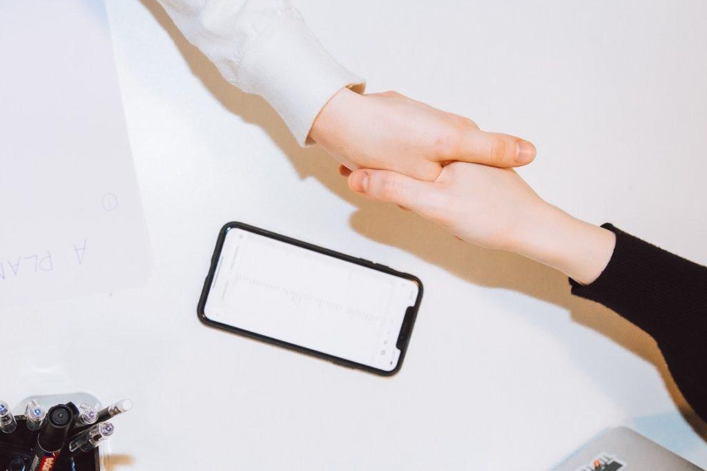 Apretón de manos entre dos personas y a su lado un teléfono móvil