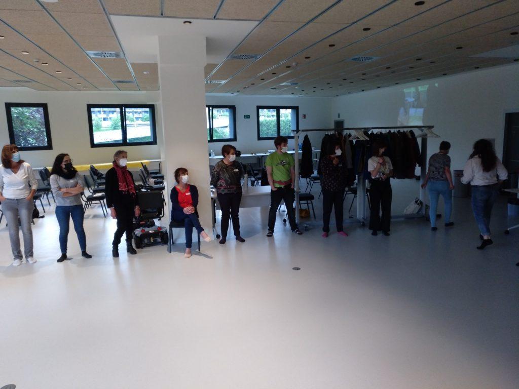 Grupo de personas en pie, en círculo, preparándose para una dinámica.