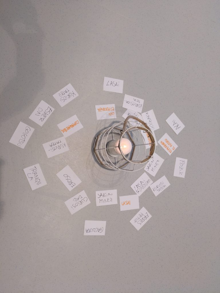 Vela encendida en un soporte y a su alrededor, etiquetas con el sentimiento expresado por las pesonas participantes.