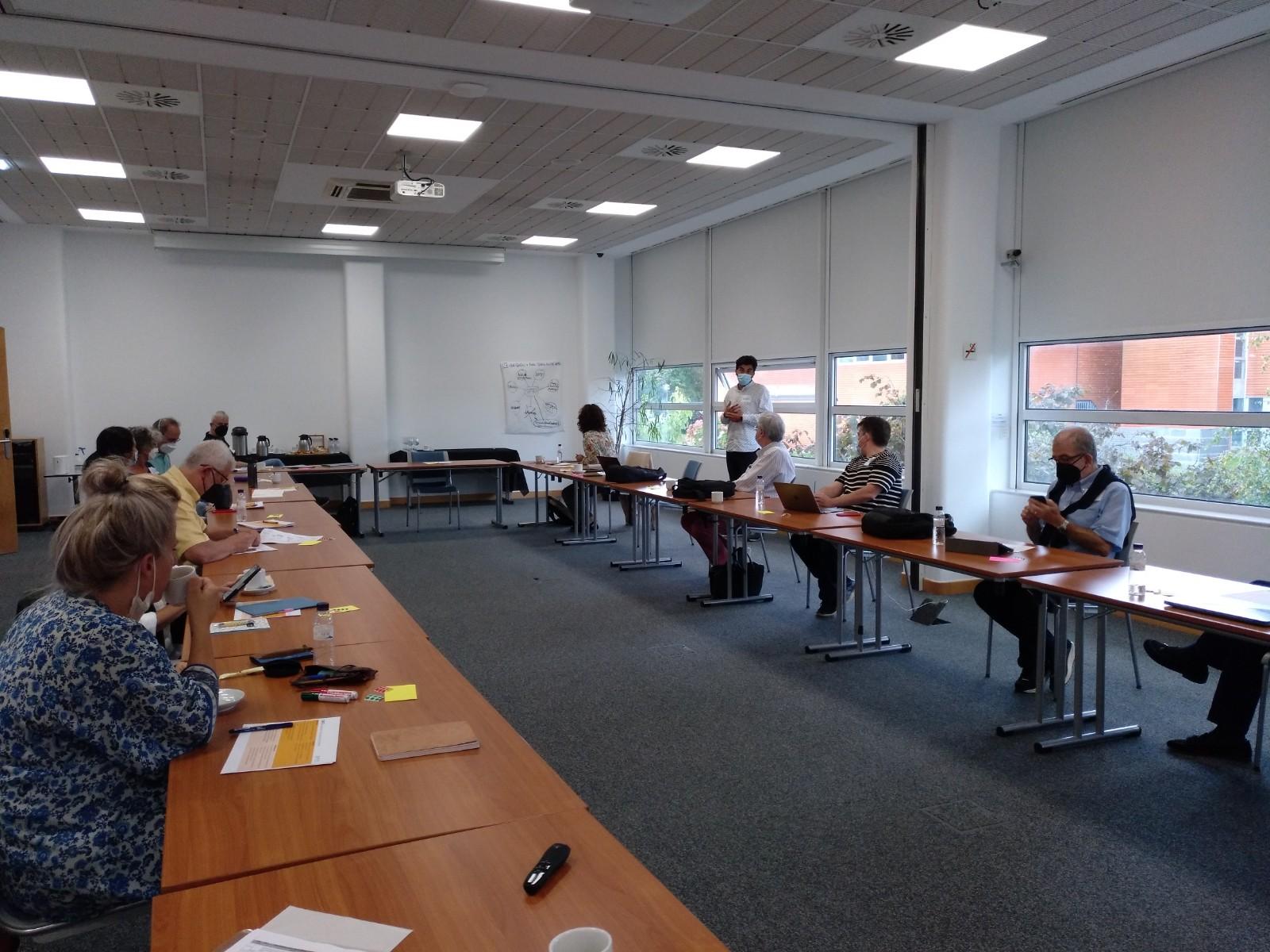 Personas sentadas alrededor de una mesa en la sesión de reflexión estratégica de APTES. Un hombre de pie, hablando hacia el resto.
